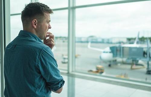 Mand med flyskræk står i lufthavnen og kigger ud på flyvemaskiner