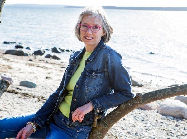 Lisbeth C. Jørgensen sidder på en træstamme på stranden